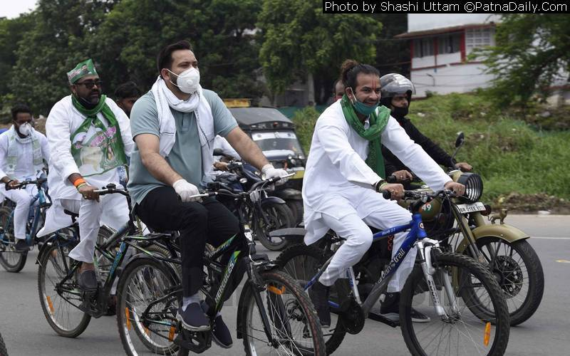 Tej Pratap and Tejaswi Yadav taking part in a cycle rally in Patna on Sunday.